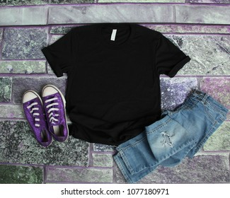 6f09da9a049c Black T Shirt mockup flat lay on purple brick background with purple shoes  and ripped jeans