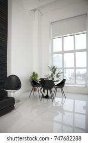 Black table and chairs in white studio.