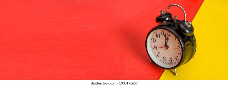 Black table clock on yellow and red banner template