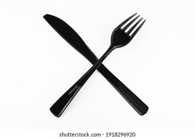 Black table fork and knife crossed on white background.