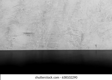 Black table in front of polished cement wall, Grey concrete loft style wall use for background.