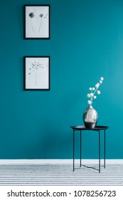Black table with a silver, flower vase and posters on green wall in anteroom interior