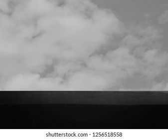 black table top with blurred cloud sky for product montage and display. black and white background.