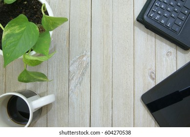 Black tablet computer, wireless keyboard and cup of coffee on a pale slatted wood surface or desk from a top down ariel view perspective and a potted house plant vine in the corner.