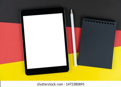 black tablet, e-book, notebook and white pencil is on flag Germany. Texture Deutsch national flag colored cardboard. Mock up, copy space, layout.