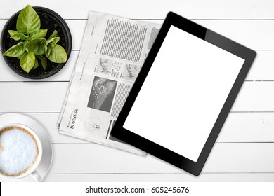 Black tablet with isolated screen and business newspaper on a wooden white table. Mock up. Lorem ipsum text.