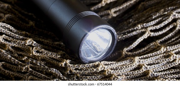Black tactical flashlight that is on brown netting