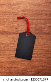 Black tag with red ribbon on wooden background. Empty place for text.
