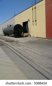 Black tank car, on railroad siding by pastel colored warehouse.Seattle,Pacific Northwest