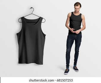 Black tank top, sleeveless t-shirt on a man in jeans, isolated, mockup. Hanging tank top, against empty wall.