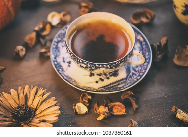 black tea in chineese porcelain cup and plate/ gzhel/ on a dark wooden table/ dried flowers/ top view