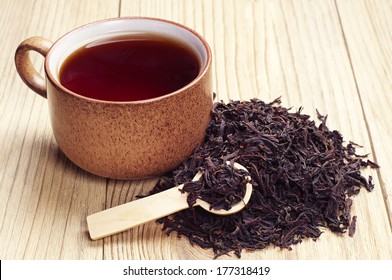 Black tea in a cup and dried leaves on wooden background