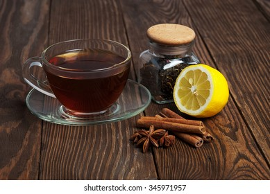 Black tea in cup of glass, lemon and cinnamon on old wooden table