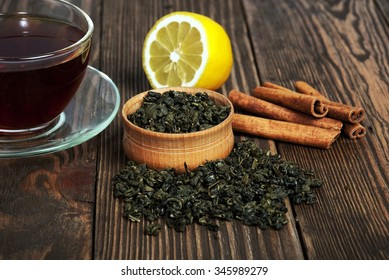 Black tea in cup of glass, lemon and cinnamon on an old wooden table