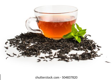 Black tea in a cup of glass. Mint and tea leaves. On white, isolated background.