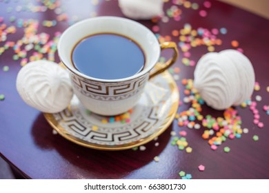 Black tea cup and sweets on the wooden table