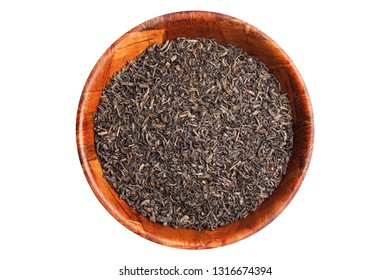 Black tea dry leaf in wooden bowl isolated on white studio background.