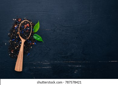 Black tea with flower petals of cornflower and dry berries. On a wooden background. Top view. Copy space.