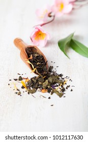 Black tea with flower petals, tea leaves and sakura on a wooden background.