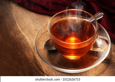 black tea freshly brewed in a glass cup, steaming hot drink on dark rustic wood, copy space, selected focus