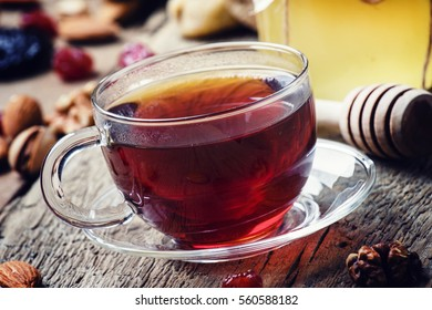 Black tea in a glass cup with honey, dried fruits and nuts, sweet, vintage wooden background, selective focus