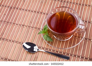 Black tea in glass cup with pepper mint and spoon