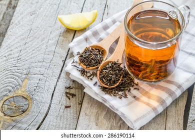 Black tea in glass cup, rustic wood background