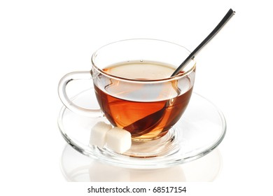 Black tea in glass cup with teaspoon and sugar cubes  isolated on white