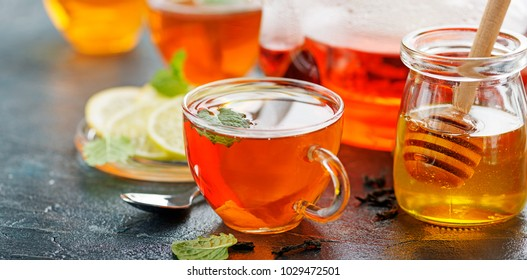 Black tea in a glass cups, mint leaves, dried tea, sliced lime and honey.