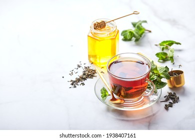 Black tea in glass transparent mug with mint leaves and honey. Calming and revitalizing tea, anti-stress and relaxation.