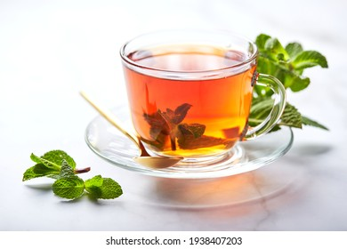 Black tea in glass transparent mug with mint leaves. Soothing tea, anti-stress.