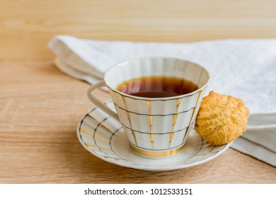 black tea in golden white cup with cocnut biscuit on wooden table closeup