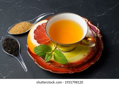 black tea with grapefruit in a cup and spoon with cane sugar