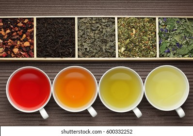 Photo of Black tea, green tea, fruit tea cups / tea assortment in boxes