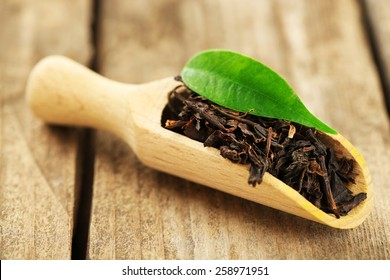 Black tea with leaf in scoop on old wooden table