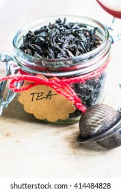 Black tea leaves in the jur with note on rustic background