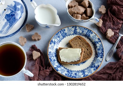 Black tea with milk and bread with butter on a blue plate. Ancient dishes in the table setting. Brown runner. Cane sugar. Photo for content. Blue and brown.