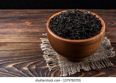 Black tea on dark wooden background.
