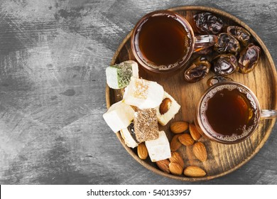 Black tea, oriental sweets, dates and nuts on a dark background. Top view, copy space. Food background