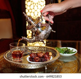 Black tea in the tea pot with mint and dates on plate, hand with tea pot and glass, food and drink, hot drinks menu card, beverages, arabic food during ramadan, iftar. Still life, objects photography