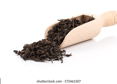 Black tea in a scoop on a black tea background. Close-up shot