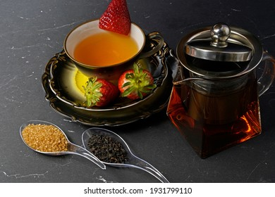 black tea with strawberry in a cup and a glass pot with tea