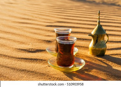Black tea in traditional glasses and pot on desert