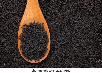 Black tea in a wooden spoon on a black tea background. Close-up.