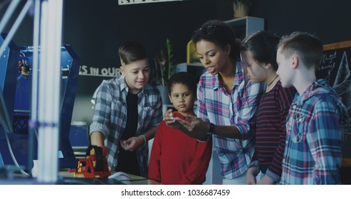 Black teacher with group of children having class about three dimensional technologies.