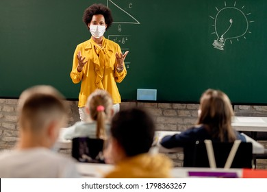 Black teacher with protective face mask teaching her students on a class at elementary school.