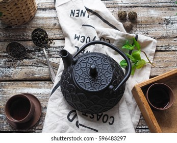 Black teapot, two bowls with green tea, mint and spoons with scattered black and green tea on an old wooden table
