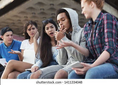 Black teen guy smoking cigarette, his friends judging him. Social issues between young people