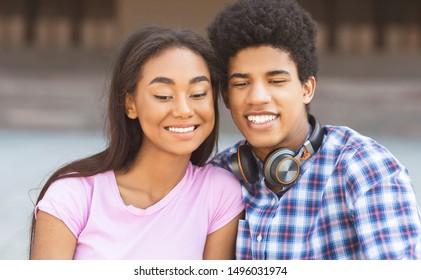 Black teenage couple posing for selfie looking down at camera on smartphone