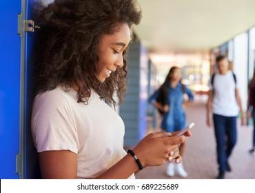 Black teenage girl using smartphone at break time in school